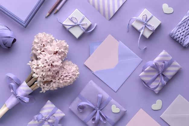 Fundo violeta da primavera com tulipas cor de rosa, jacinto, caixas de presente embrulhadas e pequenas corações
