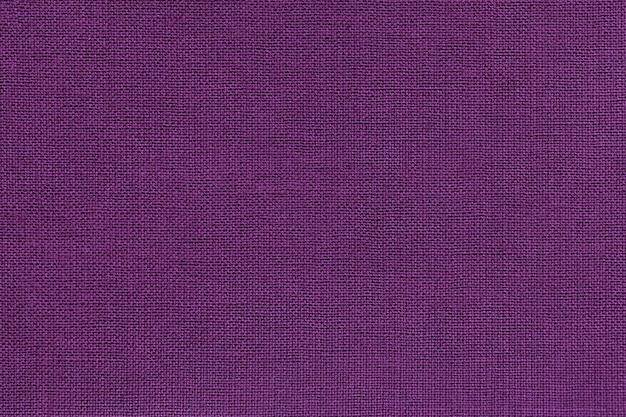 Fundo violeta escuro de um material têxtil com padrão de vime, closeup.