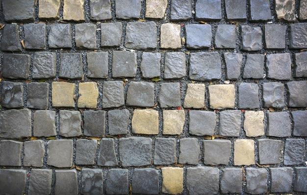 Fundos e texturas cinzentos e amarelos das pedras de pavimentação.