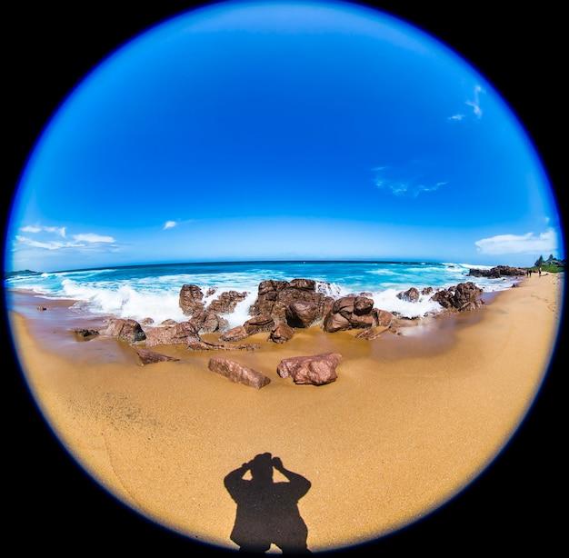 Fundos tropicais incríveis em praias paradisíacas da áfrica do sul. uma onda do mar quebra na costa rochosa. férias na costa sul-africana da rsa