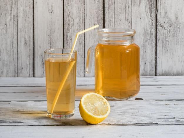 Fungo de kombucha. bebida de chá fermentado orgânico com limão em uma mesa de madeira branca.
