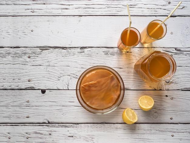 Fungo de kombucha. bebida fermentada orgânica do chá com limão em uma tabela de madeira branca, espaço da cópia.
