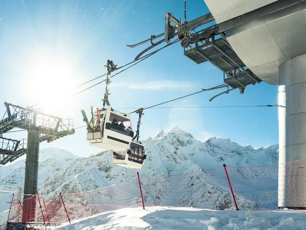 Funicular ou teleféricos com esquis e snowboards no fundo de montanhas de inverno na estância de esqui