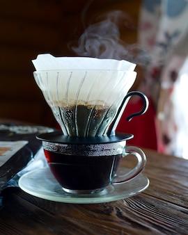 Funil de café e café em uma mesa de madeira