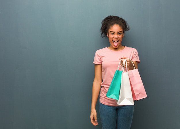 Funnny novo da mulher negra e língua mostrando amigável. ela está segurando uma sacola de compras.