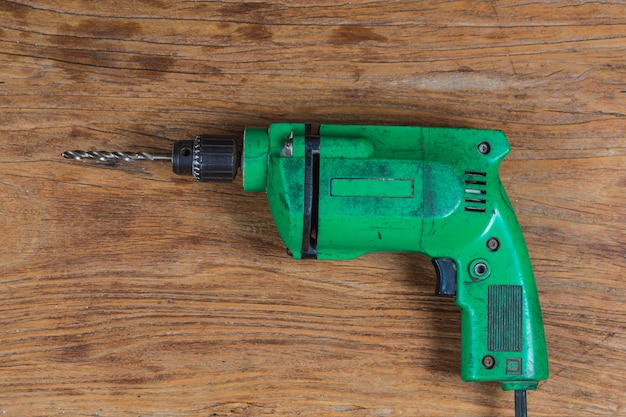 Furadeira elétrica com ferramenta de carpinteiro na placa de madeira