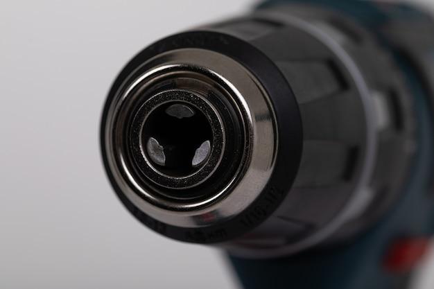 Furadeira elétrica de close-up sem broca em uma parede branca isolada