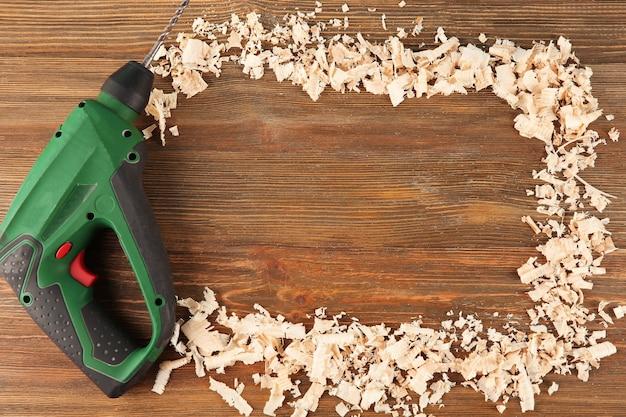 Furadeira elétrica e aparas para carpinteiro em madeira