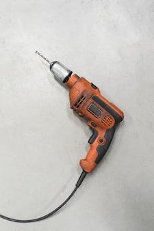 Furadeira elétrica laranja sobre piso cinza