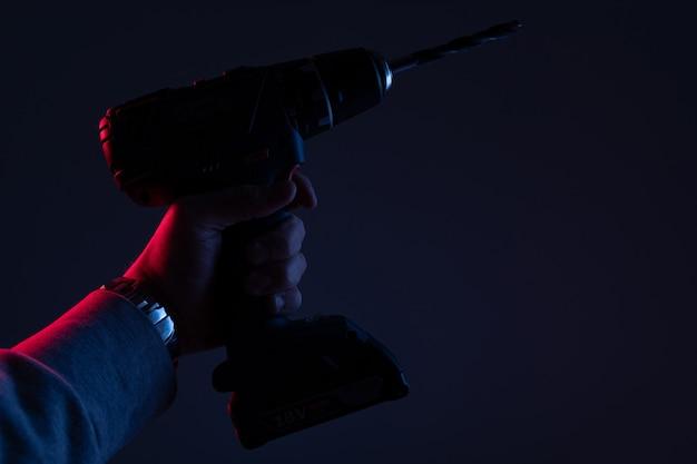 Furadeira potente para reparos em close-up com luz de néon em uma parede preta