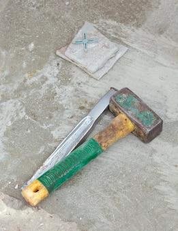 Furador e martelo no piso de concreto