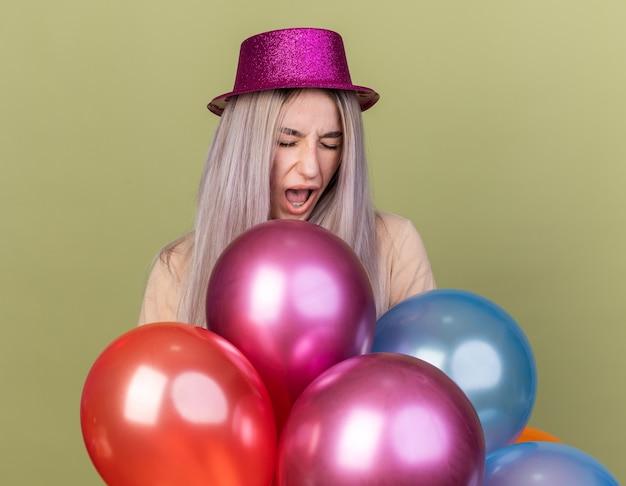 Furiosa com os olhos fechados, uma jovem linda com um chapéu de festa em pé atrás de balões