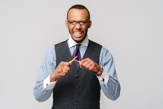 Furioso empresário afro-americano com raiva, quebrando um lápis.