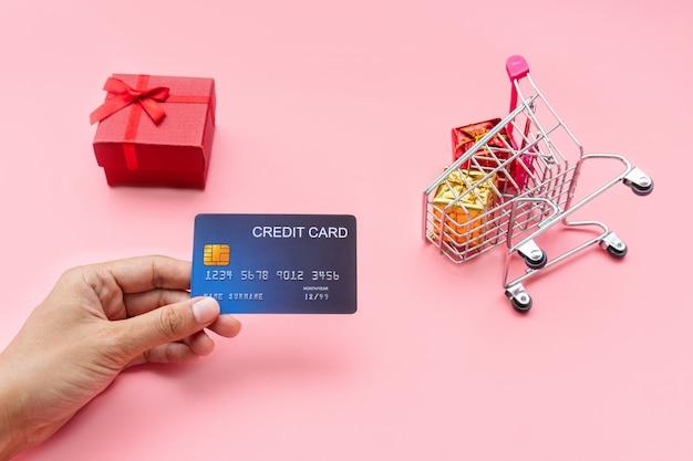 Furo de mão cartão de crédito, carrinho de compras com caixas de presente. compras, compras on-line conceito, copie o espaço, close-up