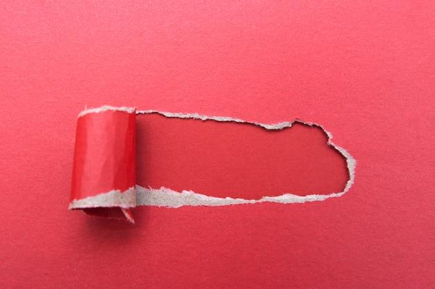 Furo em uma folha de papel vermelho sobre uma superfície vermelha