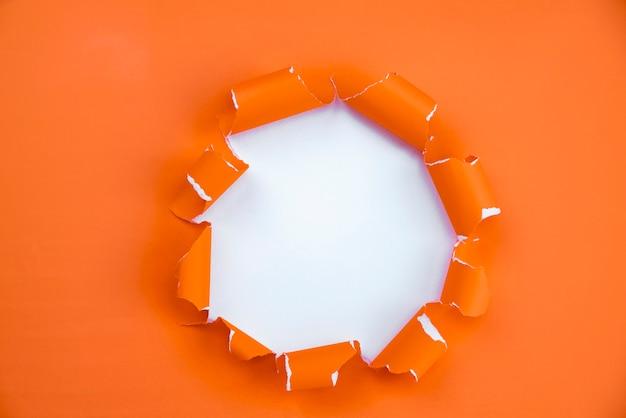 Furo no papel ou através do papel furo rasgado com avanço e espaço de design para texto em papel rasgado.