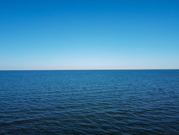Fusão de céu e mar no horizonte, água azul e céu sem nuvens.