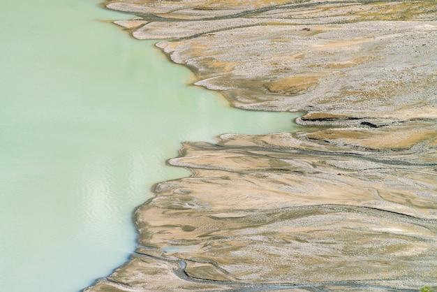 Fusão de lago e pântano nas montanhas. córregos correm pelo pântano no lago muitos riachos fluem das montanhas. água turva de cor turquesa velha. paisagem texturizada incomum da natureza de altai.