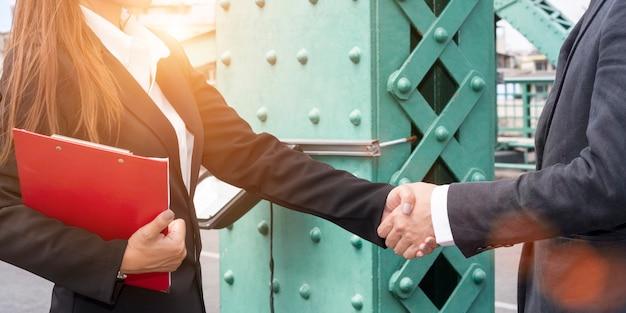 Fusão e aquisição. aperto de mão do homem de negócios do gerente com parceria da mulher.