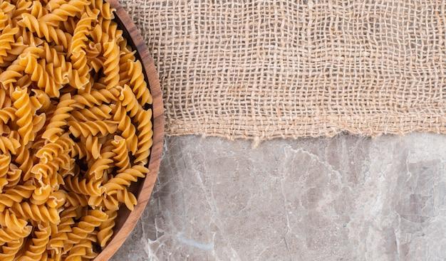 Fusilli de trigo integral cru em uma placa de madeira sobre uma serapilheira na superfície de mármore