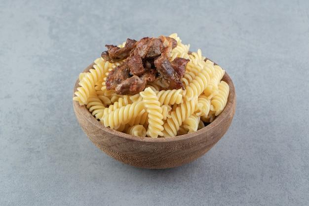 Fusilli e frango frito em uma tigela de madeira.