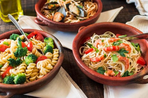 Fusilli e macarrão espaguete em louça de barro na mesa com guardanapos