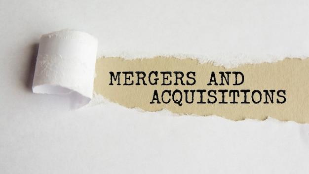 Fusões e aquisições. palavras. texto em papel cinza em fundo de papel rasgado