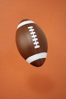 Futebol americano em fundo laranja. esporte e competição. copie o espaço. ilustração 3d