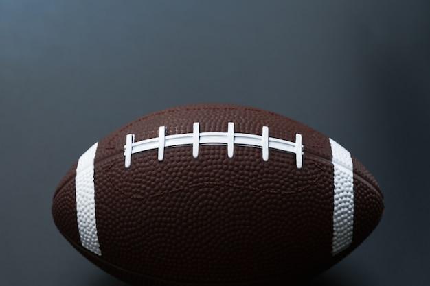 Futebol americano isolado no fundo preto. conceito de objeto de esporte