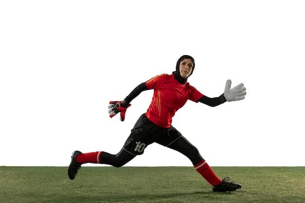 Futebol feminino árabe ou jogador de futebol, goleiro em fundo branco do estúdio. jovem mulher pegando bola, treinando, protegendo gols em movimento e ação. conceito de esporte, hobby, estilo de vida saudável.