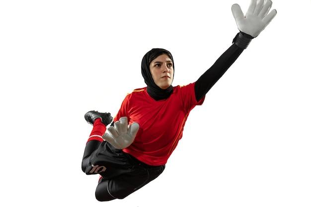 Futebol feminino árabe ou jogador de futebol, goleiro em fundo branco do estúdio. jovem mulher pegando bola, treinando, protegendo gols em movimento e ação.