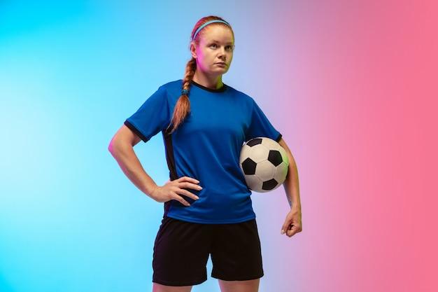 Futebol feminino, jogador de futebol treinando em ação isolado em fundo gradiente de estúdio em luz de néon