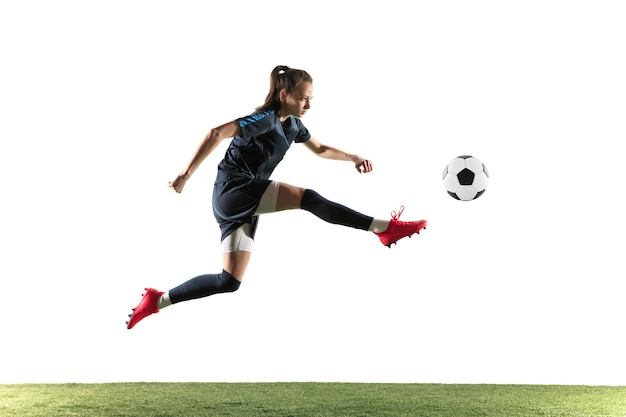 Futebol feminino jovem ou jogador de futebol com cabelo comprido em roupas esportivas e botas chutando a bola para o gol no salto isolado no fundo branco. conceito de estilo de vida saudável, esporte profissional, hobby. Foto gratuita
