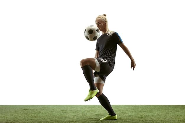 Futebol feminino jovem ou jogador de futebol com cabelo comprido em roupas esportivas e botas chutando a bola para o gol no salto sobre fundo branco. conceito de estilo de vida saudável, esporte profissional, movimento, movimento.