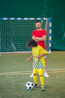 Futebol. garoto bonito em uniforme amarelo se sentindo bem na aula de educação física