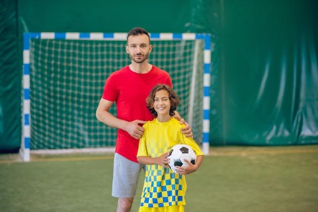 Futebol. professor de educação física com camiseta vermelha em pé perto de seu aluno segurando uma bola