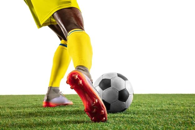 Futebol profissional afro-americano ou jogador de futebol do time amarelo em movimento isolado no fundo branco do estúdio. homem apto em ação, emoção, momento emocional. conceito de movimento na jogabilidade.