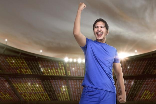 Futebolista asiática animada com camisa azul comemorando