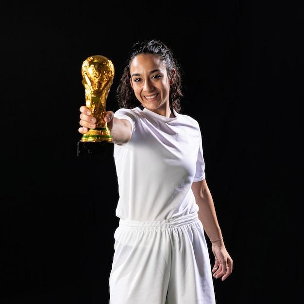 Futebolista sorridente segurando a copa do mundo