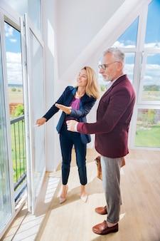 Futura casa. homem de negócios barbudo de calça cinza em pé em sua nova futura casa conversando com um corretor de imóveis