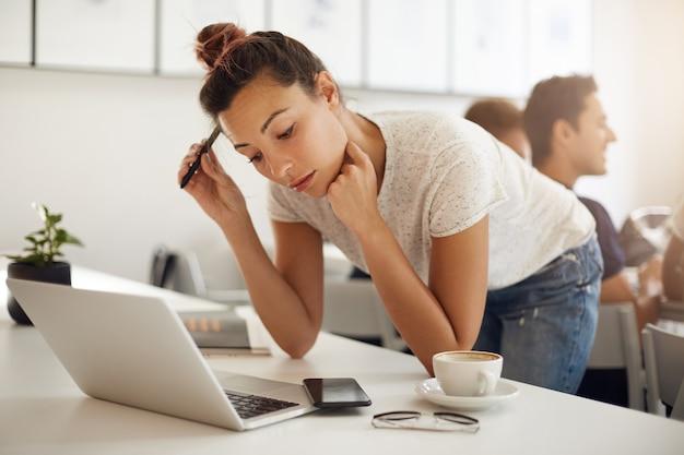 Futura designer gráfica confusa trabalhando em seu laptop em um coworking ou campus ensolarado