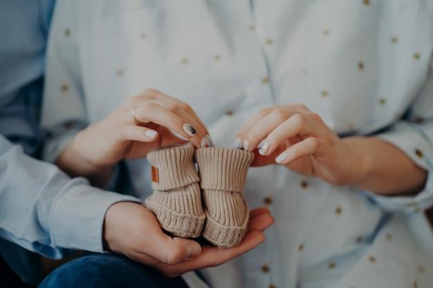 Futura mulher e homem prontos para se tornarem pais seguram sapatos infantis