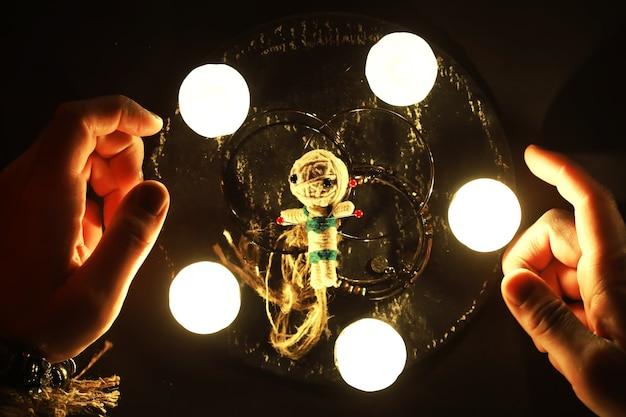 Futuro caixa. natureza morta mística com a boneca vodu, as cartas de tarô, livros, velas malignas e objetos de feitiçaria. rito de adivinhação.