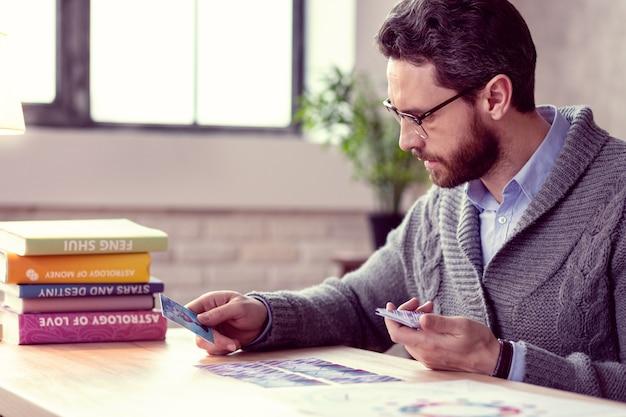 Futuro e destino. cartomante inteligente e barbudo olhando para as cartas de tarô enquanto quer saber o destino