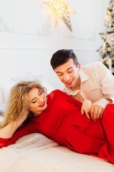 Futuros pais aguardam o bebê e sorriem na cama para a árvore de natal