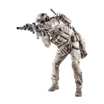 Fuzileiro da infantaria do exército moderno em uniforme camuflado, fone de ouvido de rádio no capacete, munição no transportador de carga, esgueirando-se, agachado, mirando e atirando com tiro de estúdio de rifle de serviço isolado no fundo branco