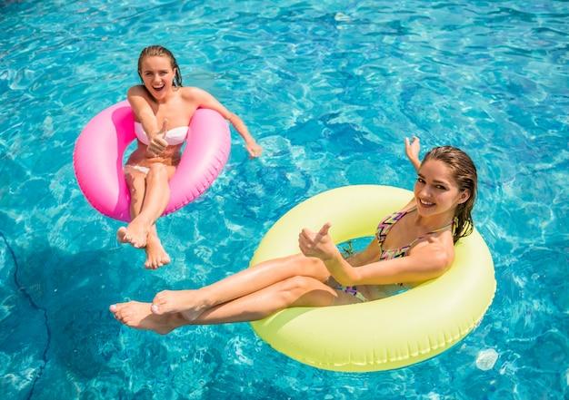 G namoradas estão se divertindo na piscina.