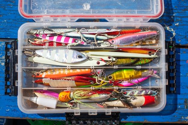 Gabarito de isca para pescar peixes marinhos na caixa de plástico na mesa de madeira azul