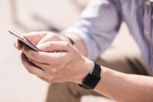 Gadget em uso. close-up de um smartphone nas mãos de um homem usando-o ao ar livre