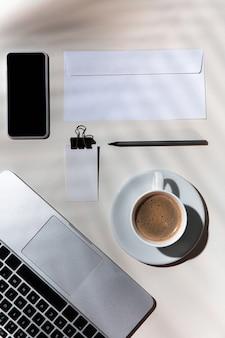 Gadgets, café, ferramentas de trabalho em uma mesa branca dentro de casa.